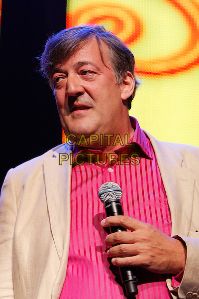 STEPHEN FRY.Performs as part of iTunes Festival 2010 at the Roundhouse, London, England, UK, July 18th 2010..half length  red shirt beige jacket on stage live stand-up show concert gig microphone  yellow.CAP/MAR.© Martin Harris/Capital Pictures.