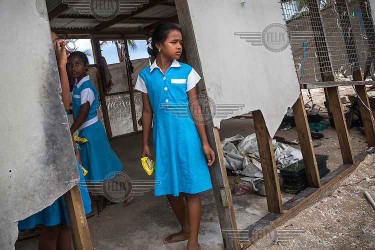11 year old Baranika (front) and her friends inspect her family's house that was badly damaged by Cyclone Pam on 10 March 2015. Nui Atoll was affected by storm surges caused by Cyclone Pam in which 12 houses were completely destroyed and 110 homes badly damaged. 71 families (40% of the population) from Nui were displaced and were living in evacuation centres or with other families. According to Tuvalu Prime Minister Enele Sopoaga estimated 45 percent of the nation's nearly 10,000 people were displaced.
