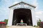 August 16, 2017; A pilgrims rests in front of the Bridgeton Covered Bridge in Bridgeton, Indiana on day 3 of the ND Trail. (Photo by Barbara Johnston/University of Notre Dame)