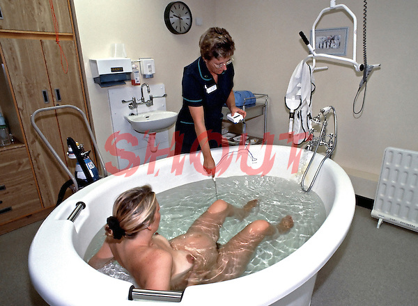 Midwife preparing the water delivery room ready for a pregnant mother to give birth. The water temperature is very important so the midwife will check the temp frequently. This image may only be used to portray the subject in a positive manner..©shoutpictures.com..john@shoutpictures.com