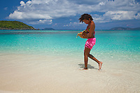Young woman at the beach with a basket of local fruit<br />