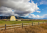 Gallatin County, MT: Yellow barn and wood fence line with clouds over the Bridger Range