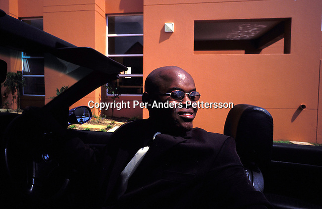 dilsbup00037.People. Buppy Oscar Dube a young successful black guy pulling out of his garage and going to work on March 22, 2002 in Johannesburg, South Africa. He is working for Ericsson, the Swedish mobile phone equipment and phone maker in South Africa. He has reached the life that many blacks want. A nice house in a mainly white gated northern suburb, a beautiful wife, and daughter and a BMW 328I Convertible. Although, he likes his success, he often goes back to Soweto on weekends to wash his car and have a few beers with his friends and relatives. Many blacks that move to the northern suburbs quickly miss the notice and lively life in the township..@Per-Anders Pettersson/iAfrika Photos