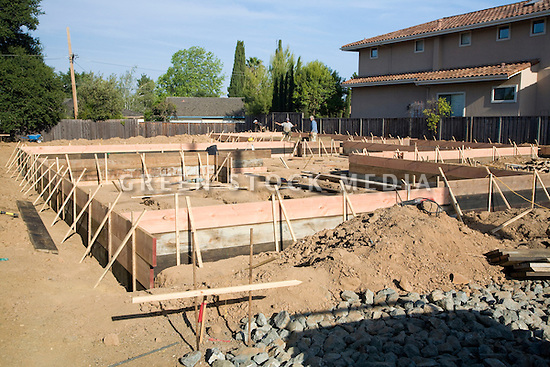 Preparation of a house foundation. Wood is used to create foundation forms that guide the pouring of concrete for a residential house foundation. Cupertino, California, USA