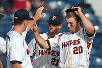 Aaron Brown (20) of the Pepperdine Waves is greeted by teammates during a game against the Oklahoma Sooners at Eddy D. Field Stadium on February 18, 2012 in Malibu,California. Pepperdine defeated Oklahoma 10-0.(Larry Goren/Four Seam Images)