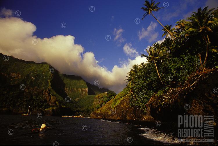 Local paddling a 'va'a' outrigger canoe past sailing yacht 'Heron', into Hanavave Bay, Marquesas, French Polynesia
