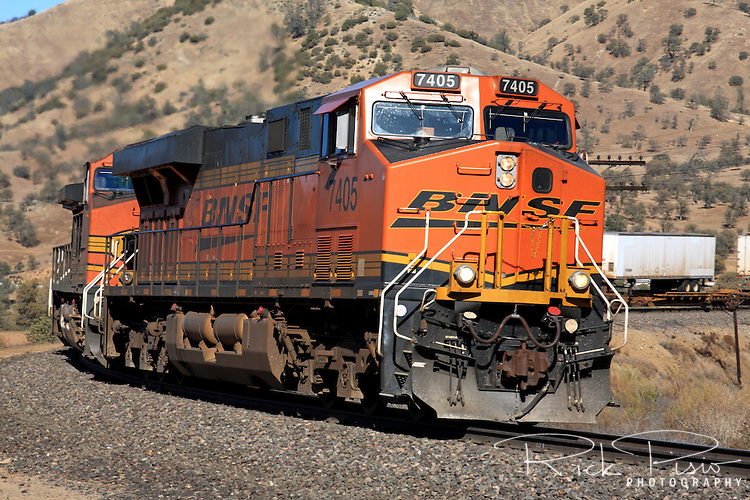 A BNSF freight train led by GE built ES44DC Locomotive 7405 climbs the grade eastbound near the Tehachapi Loop. The The ES44DC is an Evolution Series locomotive with 4400 HP and DC traction motors.
