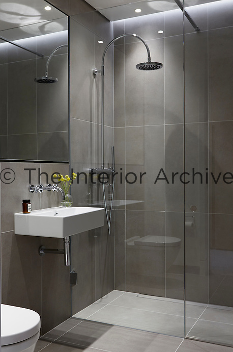 The grey tiled bathroom is cool and stylish with a walk-in shower and wall mounted hand basin.
