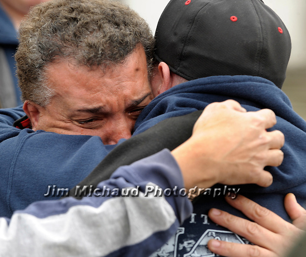 (Fitchburg Ma 041814) Sandrino Oliver uncle of Jeremiah Oliver, is comforted by searcher Miguel Fietas,  while crying and repeatedly screaming the name Jeremiah, later collapsing,  the body fitting the size and age of Jeremiah Oliver was found on the side of I-190 earlier in the day, Friday, April 18, 2014, at a small memorial  on Kimball Street in Fitchburg. (Jim Michaud Photo) For Saturday