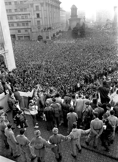 ROMANIA, Pta. Palatului, today Pta. Revolutiei, Bucharest, 22.12.1989<br /> People rise against Ceausescu. After the Ceausescu couple has fled by helicopter around noon, protestors fill the square which originally was guarded by tanks. They aim at the Communist Party Central Committee building. Its balcony is climbed, revolutionary speeches are made. Still security forces try to hamper the new spirit of freedom and democracy.<br /> © Andrei Pandele / EST&OST