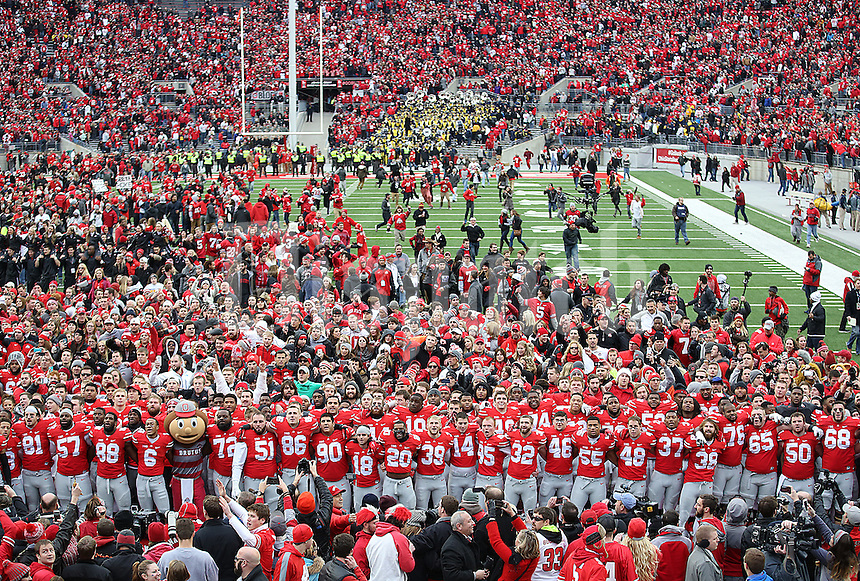 The fans take the field as the players stand in front of the band during the playing of Carmen Ohio after the victory over Michigan at Ohio Stadium on November 29, 2014. (Chris Russell/Dispatch Photo)