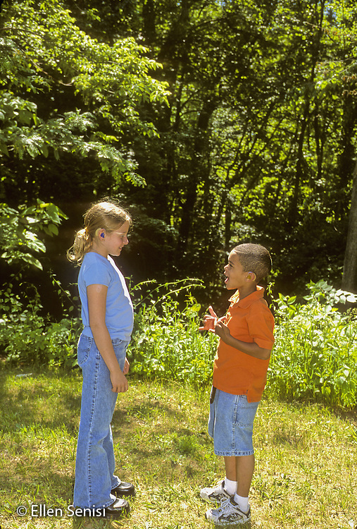 MR / Guilderland, New York. Westmere Elementary School. BOCES Deaf and HOH Class. Deaf students sign using ASL at recess. Gender differences in growth can be seen. Girl: 10, deaf; Boy: 9, African American and Caucasian, deaf. MR: Bli1 Mcg2 © Ellen B. Senisi