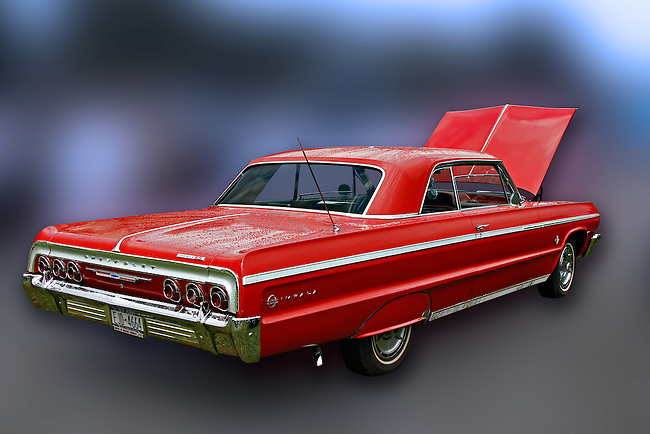 Fire-engine red sporty Impala with chrome trim stands alone against a blurred, blue and gray background camouflaging the environment at the 2010 Wings 'n' Wheels Showcase, Galway, New York. Photographed showing the tail and passenger side, with the hood up, highlights the Impala's sleek lines.
