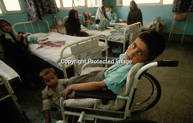 COAFGHA35064.Country. Afghanistan. Kabul. Victims of mines in a hospital. Boy in a wheelchair and children lying on beds. 9/96.©Per-Anders Pettersson/iAfrika Photos