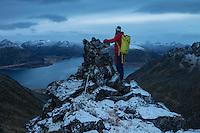 Female hiker stands next to summit cairn on Persatind, Gimsøy, Lofoten Islands, Norway