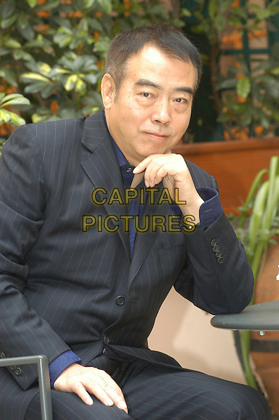 CHEN KAIGE.Photocall with Chen Kaige at the opening of the Asian Film Festival, Rome, Italy..December 6th, 2006.half length black suit sitting. CAP/CAV.©Luca Cavallari/Capital Pictures