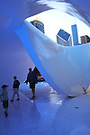 People walk under the Burnham Pavilion designed by Zaha Hadid in Millennium Park in Chicago, Illinois on July 23, 2009.