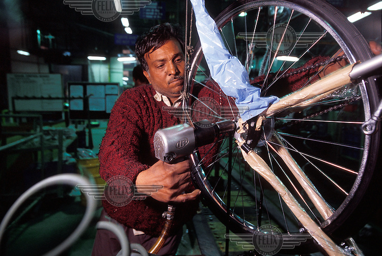Worker at Hero Cycles, the largest bicycle factory in the world. Much of the assembly machinery has come from the Taiwanese cycle manufacturer, Giant.