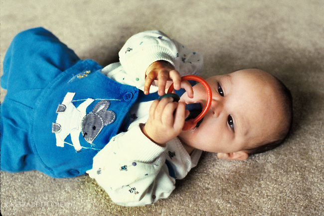 Oakland, CA Baby girl, six-months-old showing convergence of eyes while studying rattle toy
