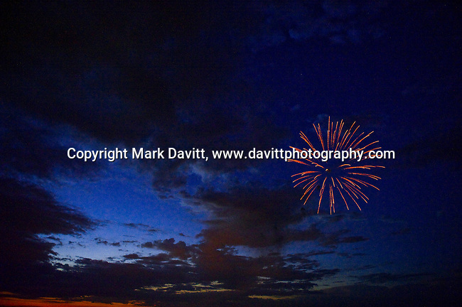 Fireworks in single burst with a cloudy sky