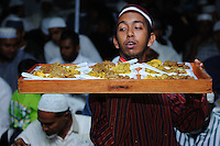 Muslim man delivering meal tray curiously while checking guests. Taken at ceremony of prophet Mohammad's holy birth week celebration in Suriname.