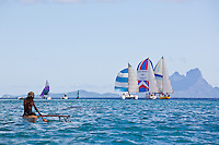 Tahitian man paddling small outrigger canoe off Tahaa island with Bora Bora and yachts with spinnakers in background