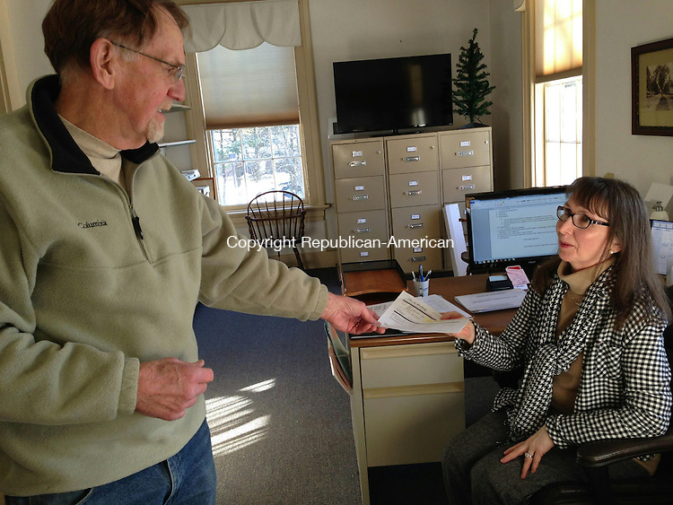 WOODBURY, CT - 3 Jan 2014 - 010314RH02 - First Selectman William J. Butterly Jr., left, passes a paper to his administrative assistant, former Plymouth Mayor Jan A. Krampitz. Rick Harrison Republican-American