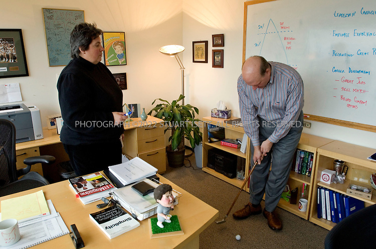 1/23/2006--Redmond, WA, USA..12:06pm: Steve Ballmer, CEO of Microsoft, putts golf balls during a meeting with Lisa Brummel, Senior Vice President of Human Resources, in her office just down the hall from Ballmer's office. The meeting was to discuss Microsoft personnel matters. Ballmer often plays with his putter while in Brummel's office...Photograph ©2007 Stuart Isett.All rights reserved