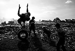 A group of boys who live and work at the dump in Chinandega pass time by diving into a pile of peanut shells using an old tire as a springboard.