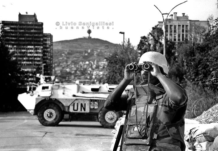 Sarajevo / Bosnia 1994<br /> Un casco blu del contingente francese della missione di pace Unprofor controlla le postazioni serbo bosniache lungo lo Sniper Allee (Viale dei cecchini). French blu helmet of Unprofor peacekeeping mission monitors bosnian serb army positions along the Snipers Allee.<br /> Photo Livio Senigalliesi