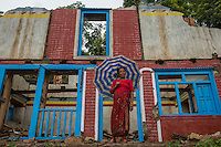 Nepal, Sindhulpalchowk District,. Earthquake recovery and relief efforts during the summer monsoon rains. Families that lost their homes living in temporary shelters. Ramda Chewati in front of her damaged home.