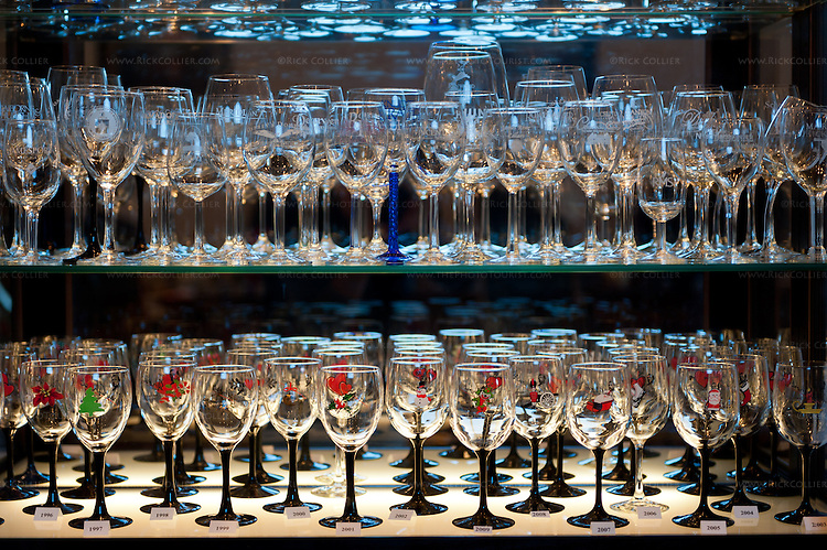 A collection of themed wine glasses is displayed in a glass cabinet in the tasting room at Gray Ghost Vineyards.