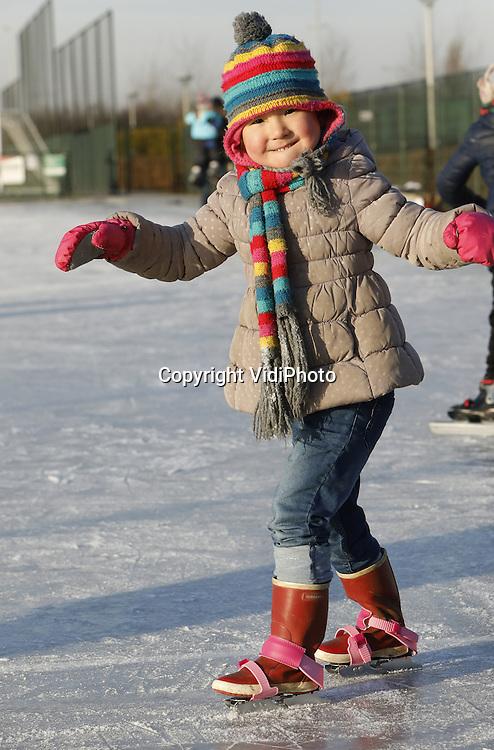 Foto: VidiPhoto<br /> <br /> ARNHEM - Winterpret op de ijsbaan in Arnhem vrijdag. Als eerste schaatsbaan van Nederland met natuurijs en na slechts &eacute;&eacute;n nacht van flinke vorst, ging schaatsbaan De Schuytgraaf in Arnhem-Zuid vrijdag al open voor het publiek. Daar werd op de laatste dag van de Kerstvakantie volop gebruik van gemaakt door schaatsliefhebbers uit de wijde regio. Ook afgelopen jaren De Schuytgraaf de eerste schaatsbaan in Nederland met berijdbaar natuurijs. Vrijwilligers van schaatsvereniging STG Rijnijssel zijn samen met medewerkers van de gemeente Arnhem de hele nacht in de weer geweest om een paar centimer dik ijs te construeren. De ondergrond wordt gevormd door het asfalt van de skeelerbaan.