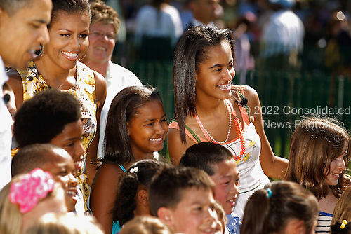 United States President Barack Obama, first lady Michelle Obama and their daughters Sasha and Malia pose for photographs with children after officially opening the White House Easter Egg Roll on the South Lawn of the White House, Monday, April 25, 2011 in Washington, DC. About 30,000 people are expected to attend the 132-year-old tradition of rolling colored eggs down the White House lawn. .Credit: Chip Somodevilla / Pool via CNP