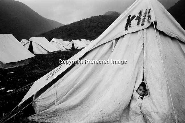 A refugee boy looks out of his family tent on April 21, 1999 in a refugee camp in Cegrane, Macedonia. Tens of thousands of people fled from Kosovo from Serb terror into Albania and Macedonia in early 1999. The international community entered Kosovo in June 1999 and the Serb occupants retreated to Serbia. (Photo by: Per-Anders Pettersson)