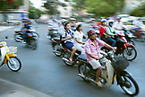 VIETNAM, Saigon, Ho Chi Minh City, mopeds buzz around a busy street corner in the city center