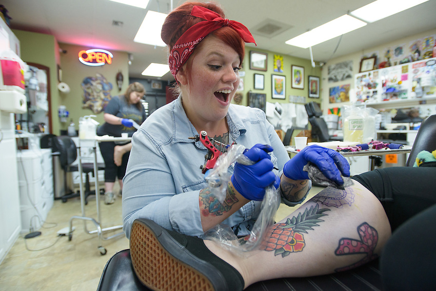 Brie Felts works on Valerie Gunther's tattoo at Primal Instinct Tattoo. Photo by James R. Evans