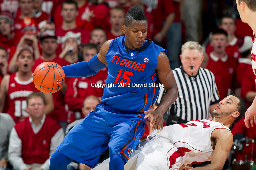 Florida Gators forward Will Yeguete (15) handles the ball against Wisconsin Badgers guard Traevon Jackson (12) during an NCAA college basketball game Tuesday, November 12, 2013, in Madison, Wis. The Badgers won 59-53. (Photo by David Stluka)