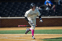 Kevin Conway (7) of the Wake Forest Demon Deacons flips his bat as he starts down the first base line against the Virginia Tech Hokies at Wake Forest Baseball Park on March 7, 2015 in Winston-Salem, North Carolina.  The Hokies defeated the Demon Deacons 12-7 in game one of a double-header.   (Brian Westerholt/Four Seam Images)