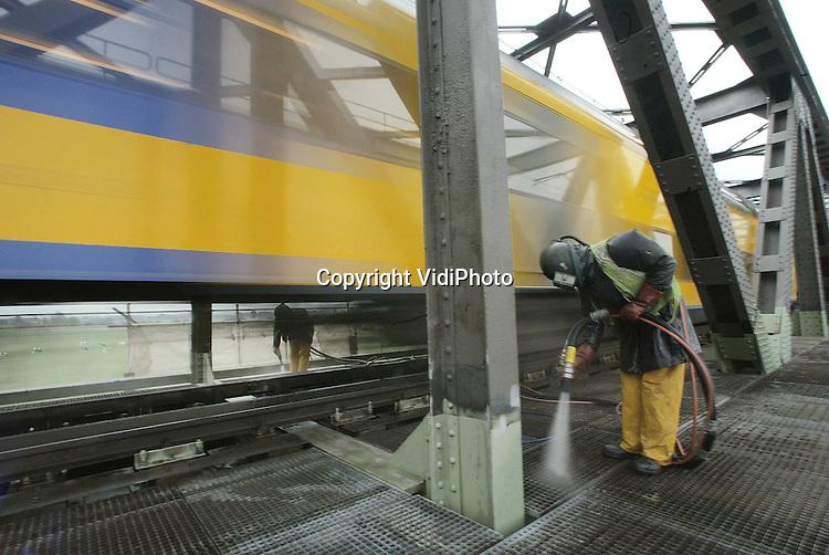 Foto: VidiPhoto..HEDEL - Personeel van schildersbedrijf Holland uit Rotterdam werkt de komende drie jaar nog aan de spoorbrug over de Maas bij Hedel. De oeververbinding krijgt in opdracht van Railinfrabeheer een grote verfbeurt. Ongebruikelijk is dat er twee verschillende componenten alluminium-verfsoorten over elkaar worden gebruiken. Voordeel is echter dat hierdoor de onderste coating niet weggehaald hoeft te worden. De verfspatten op het rijdek worden vervolgens onder hoge druk weggestraald.