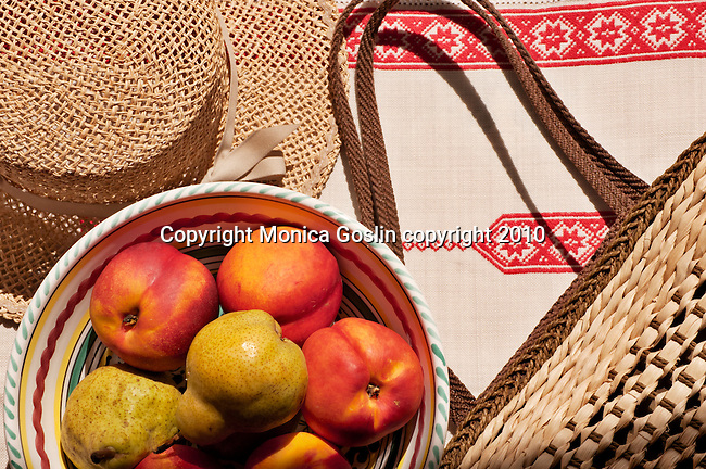 Straw bag from Bellagio, Italy with a straw hat and a bowl of fruit