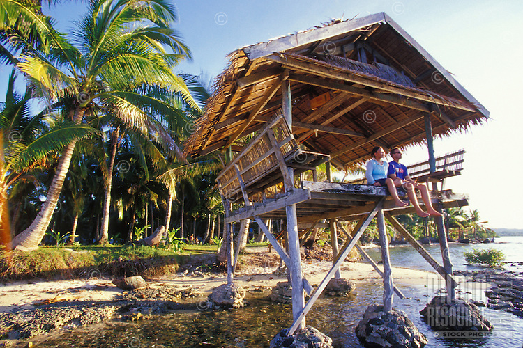 Couple in thatched hut on the ocean at sunset, Siargao Island, Philippines
