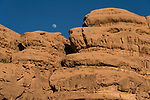 The moon over eroded sandstone formations in the Wadi Rum Protected Area, a UNESCO World Heritage Site.   Hashemite Kingdom of Jordan.