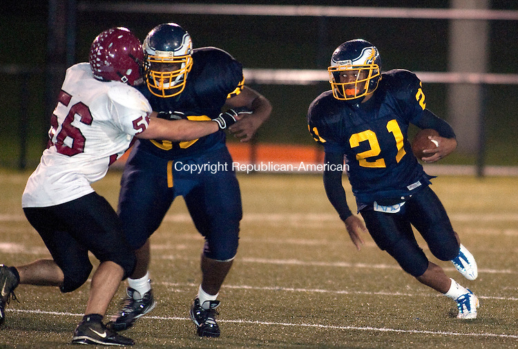WATERBURY, CT, 15 OCTOBER 2010-101510JS06-Kennedy's Devon Petty (21) gets to the open field with the help of a block by teammate Oswald Jean Baptiste (68)  on Torrington's Dominic Sansone (68) during their game Friday at Municipal Stadium in Waterbury. <br />  Jim Shannon Republican-American