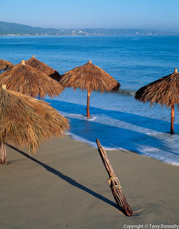 Nayarit, Mexico<br /> Thatched Pallapas on the beach in the village of Bucerias with Bahia de Banderas (Banderas Bay) and Punta de Mita in the distance