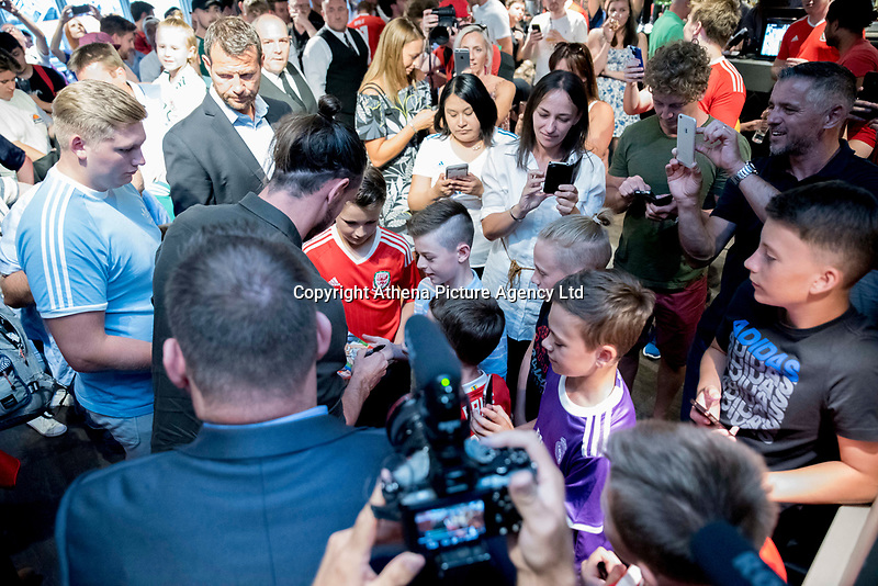 """Pictured: Gareth Bale signs autographs at his Elevens Bar in Cardiff, Wales, UK. Thursday 12 July 2018<br /> Re: Last night (Thurday 12 July) Elevens Bar & Grill and the Football Association of Wales jointly hosted a Q&A evening with Gareth Bale. At the event, Gareth unveiled a new piece of memorabilia for Elevens – his match worn boots from this year's Champions League Final with which he scored that incredible overhead kick.<br /> The event, hosted at Elevens Bar & Grill was open to members of the public with doors opening at 6pm on Thursday evening. People started queueing from 3pm, with a cross-section of fans of all ages in Wales shirts and bucket hats. <br /> The Q&A, conducted by Ian Gwyn Hughes from the FAW, discussed all aspects of his career so far, from growing up in Cardiff to winning 4 Champions League medals with Real Madrid. On growing up in Whitchurch, Gareth said: """"My family were a huge influence on me growing up. My parents were so supportive, taking me here there and everywhere so I could play football. Growing up I can hardly remember not being with a football – I even took one to bed!""""<br /> There were a lot of youngsters in the audience, eager to hear from their hero. Gareth's advice to them? """"Work hard for what you want and who knows where that could take you.""""<br /> As a left-footer, Ryan Giggs,  Wales' national team manager was someone he looked up to growing up. Gareth mentioned it was great to beat Ian Rush's goal scoring record for Wales with his childhood idol as manager. """"I knew I'd levelled his record at half time, I needed one more to break it. The manager wanted to take me off but I said give me another 15 minutes to see if I can do it. Luckily on 61 minutes our goalkeeping coach took too long to do the substitution on the paper, so it gave me an extra minute. It worked out perfectly."""""""