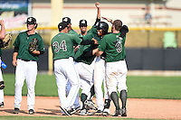 Clinton LumberKings second baseman Martin Peguero (7) is mobbed by teammates including Carlos Misell (34) and Brett Thomas (8) after a game winning hit during a game against the Beloit Snappers on August 17, 2014 at Ashford University Field in Clinton, Iowa.  Clinton defeated Beloit 4-3.  (Mike Janes/Four Seam Images)