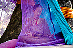 A Buddist visitor in Bodh Gaya, under the tree, protected by the colourful nylon mosquito net, concentrates on her beads for meditation. Photograph © Santosh Verma