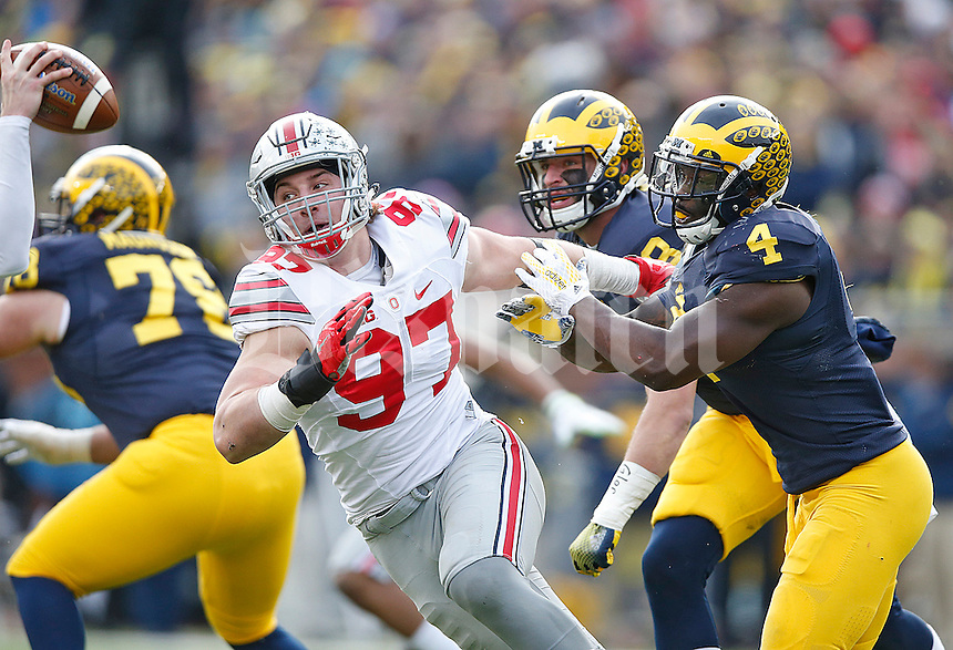 Ohio State Buckeyes defensive lineman Joey Bosa (97) gets a bead on Michigan Wolverines quarterback Jake Rudock (15) as he rushes past Michigan Wolverines defensive end Reuben Jones (4) at Michigan Stadium on November 28, 2015. (Chris Russell/Dispatch Photo)