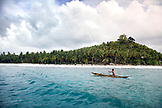 INDONESIA, Mentawai Islands, Kandui Surf Resort, native man in a dugout canoe with palm trees in the background, Indian Ocean